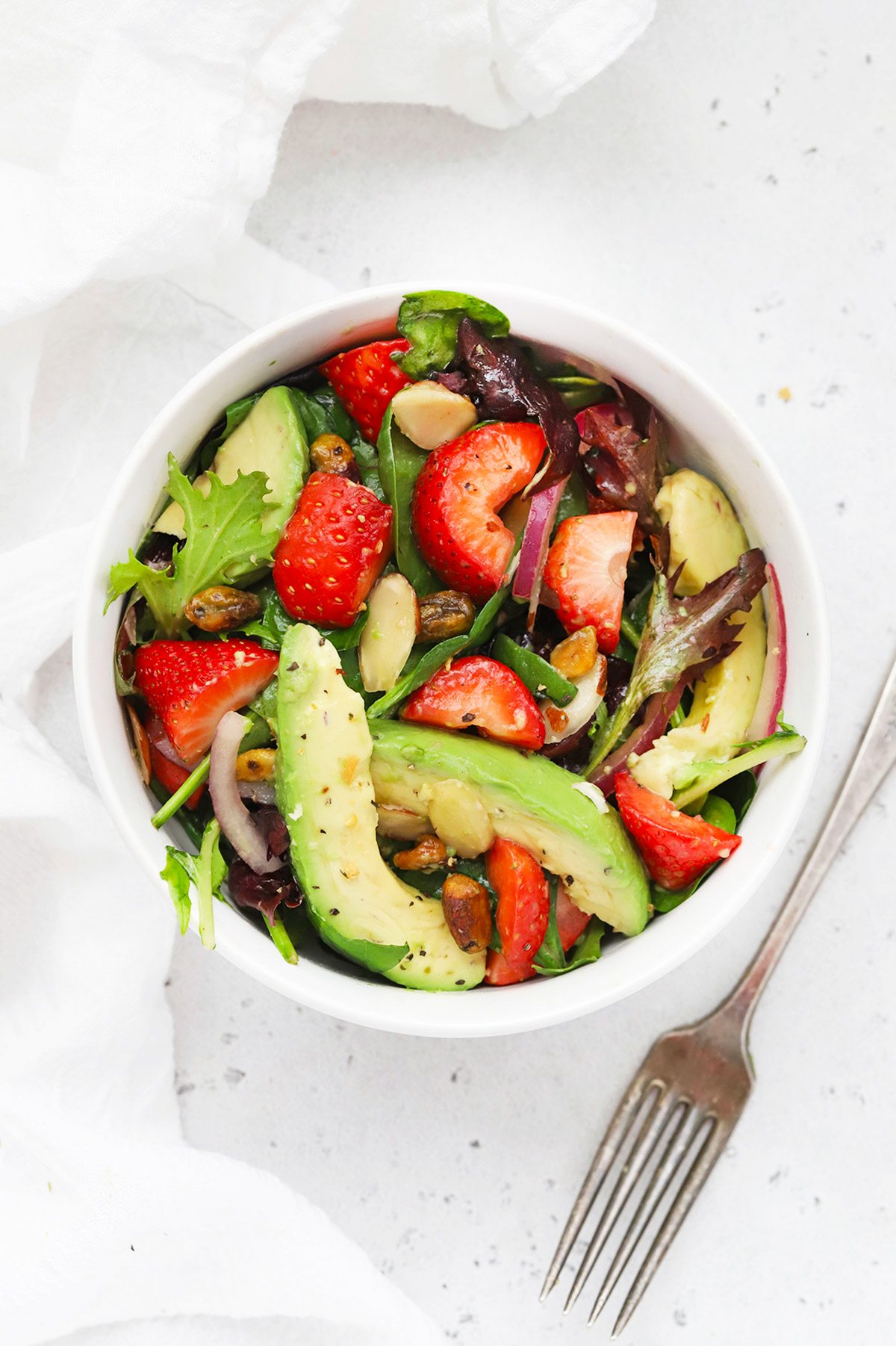 Overhead view of a white bowl of strawberry spinach salad and a fork on a white background