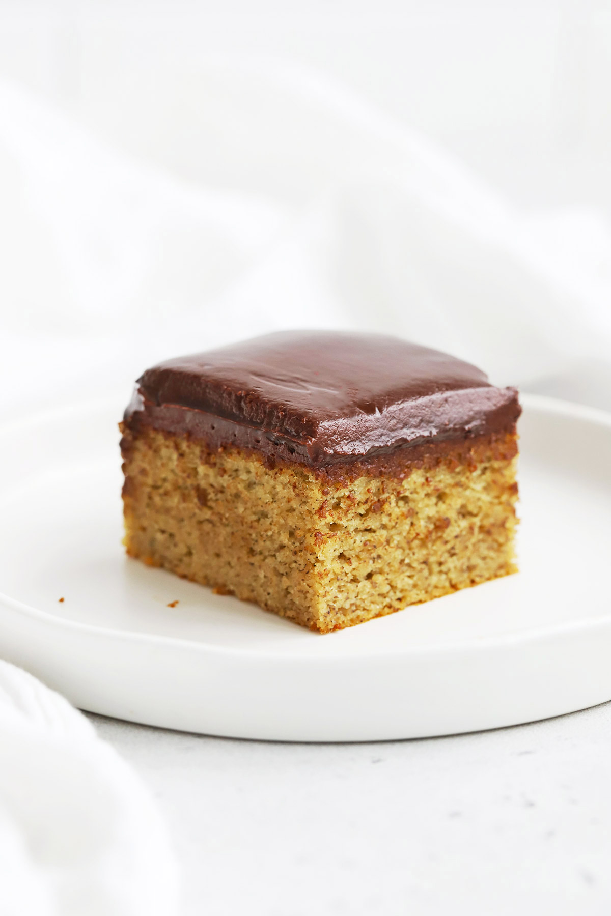 Front view of a slice of almond flour banana cake with chocolate ganache on a white plate