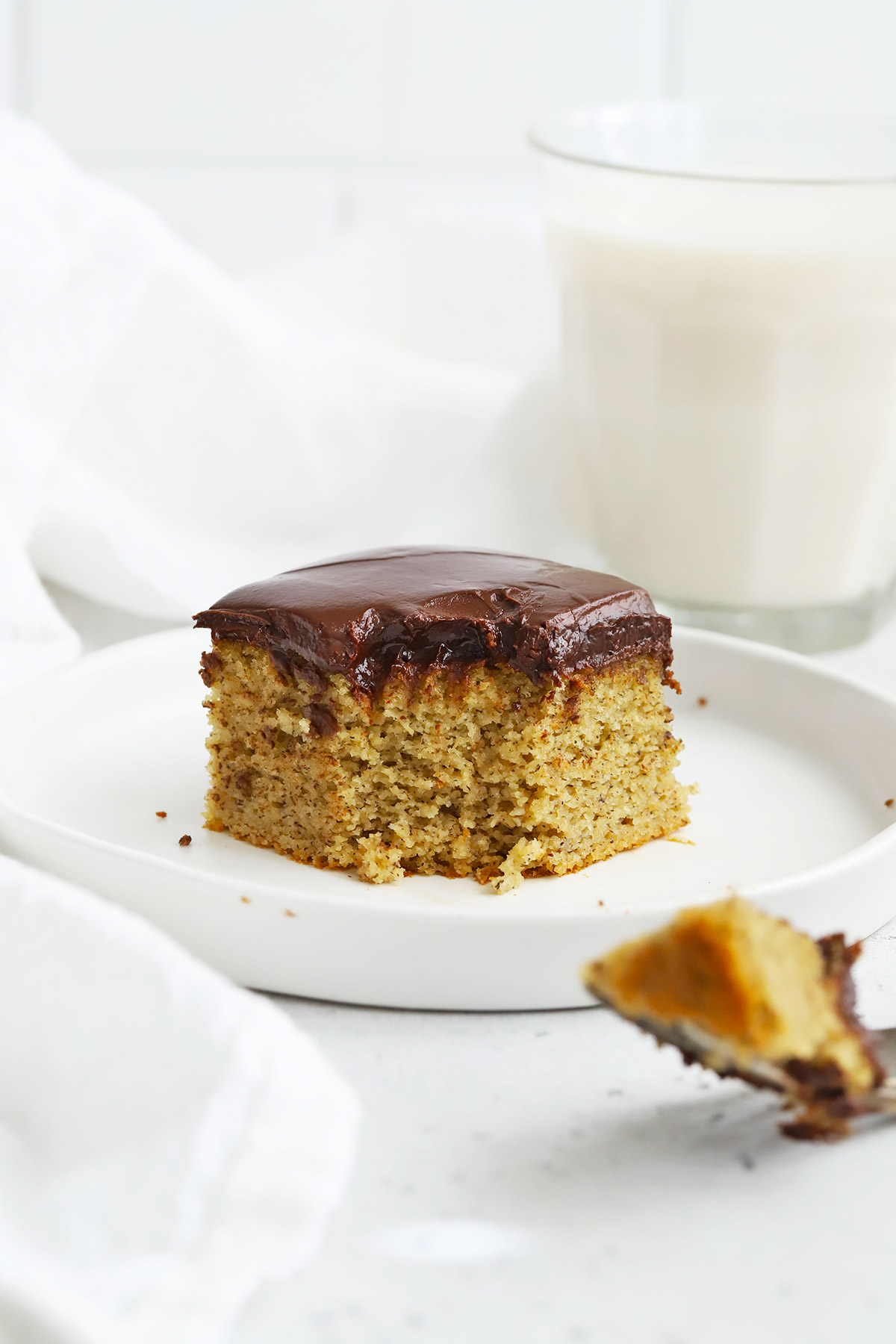Front view of a slice of almond flour banana cake on a white plate with a bite taken out of it