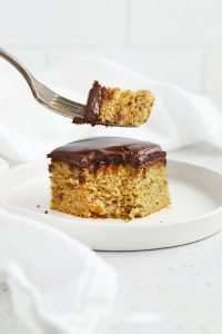 Front view of a fork taking a bite out of a slice of almond flour banana cake on a white plate