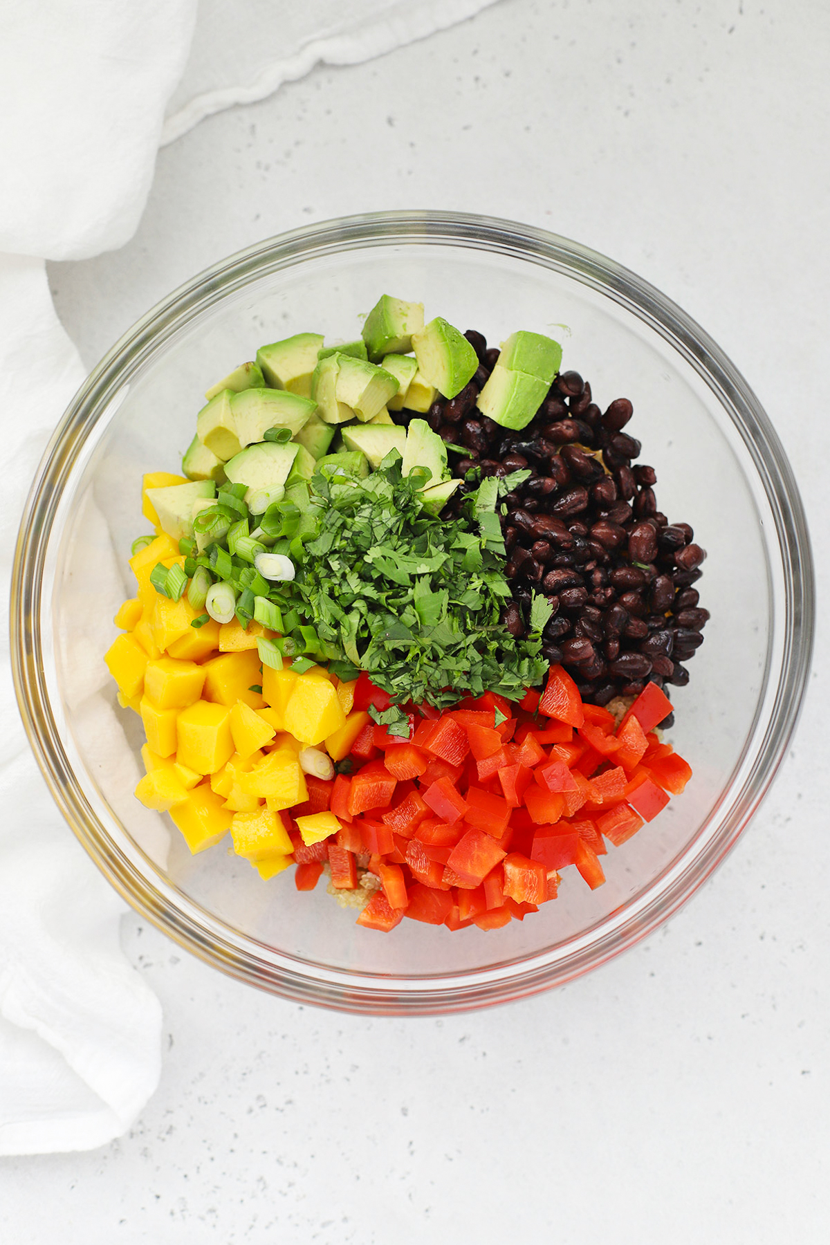 Overhead view of Confetti Quinoa Salad being assembled with bell peppers, black beans, avocado, mango, green onion, and cilantro.