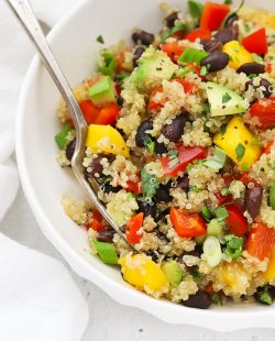 Close up Front view of a bowl of Confetti Quinoa Salad in a white bowl on a white background