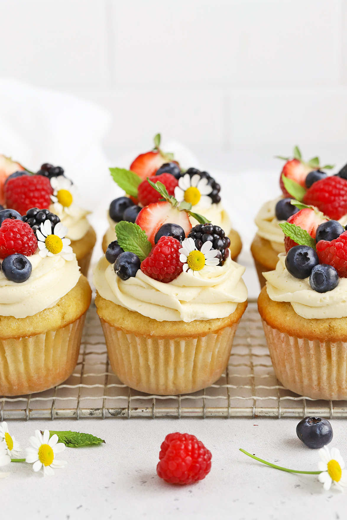 Front view of gluten-free lemon cupcakes with lemon frosting, fresh berries, and edible flowers on a white background