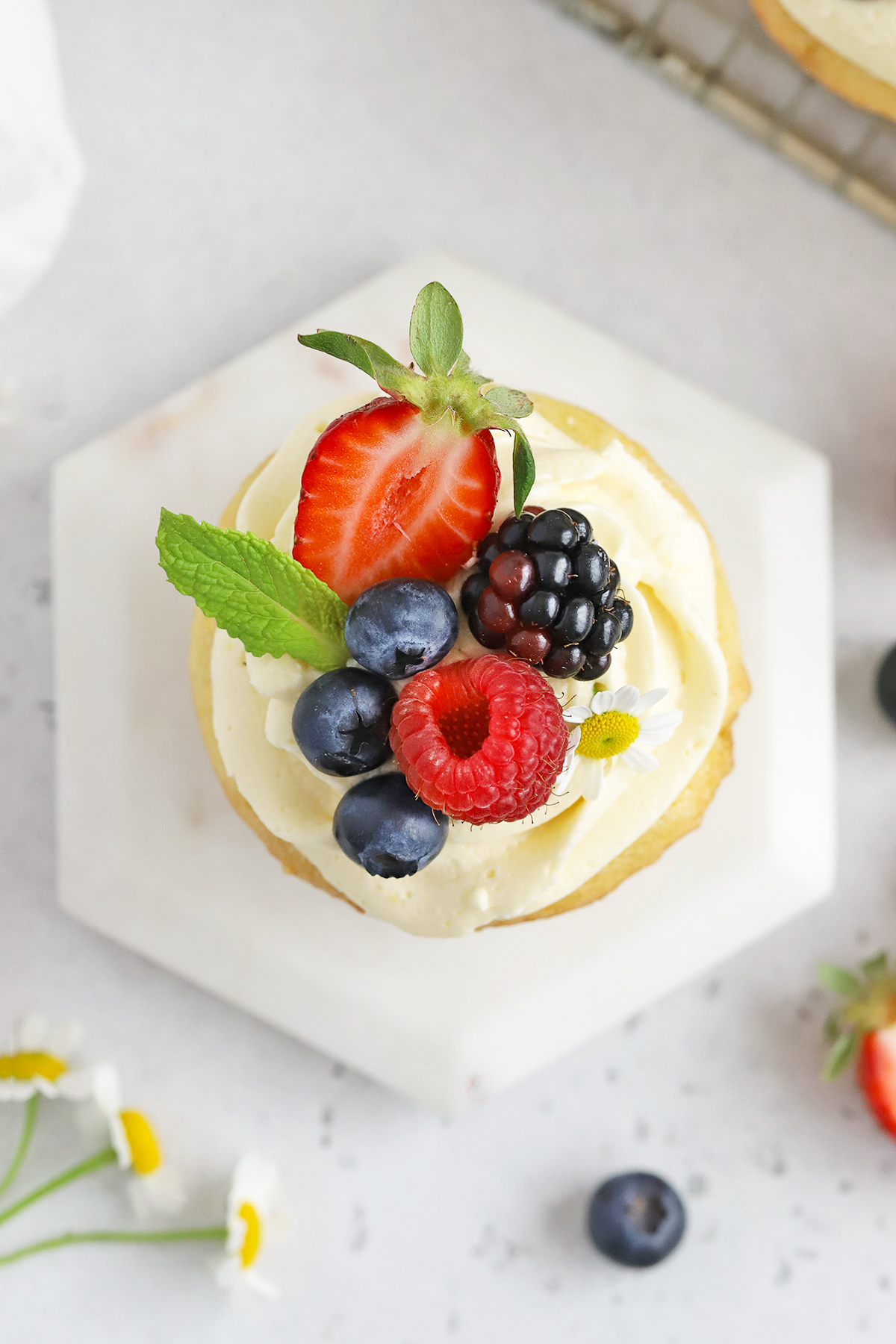 Overhead view of a gluten-free lemon cupcake with lemon frosting, fresh berries, and edible flowers on a white background