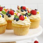 Front view of gluten-free lemon cupcakes with lemon frosting, fresh berries, and edible flowers on a white cake stand