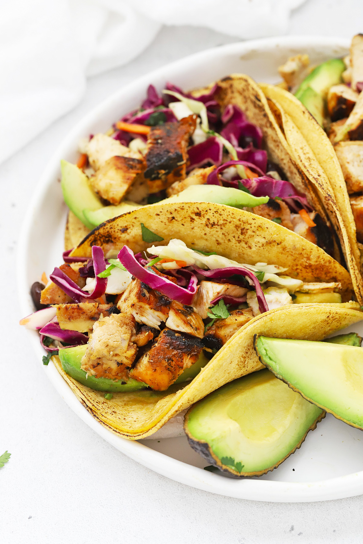 Front view of three honey lime chicken tacos with slaw on a white plate