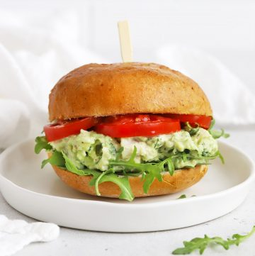 Front view of an avocado chicken salad sandwich with tomato and arugula on a white plate.