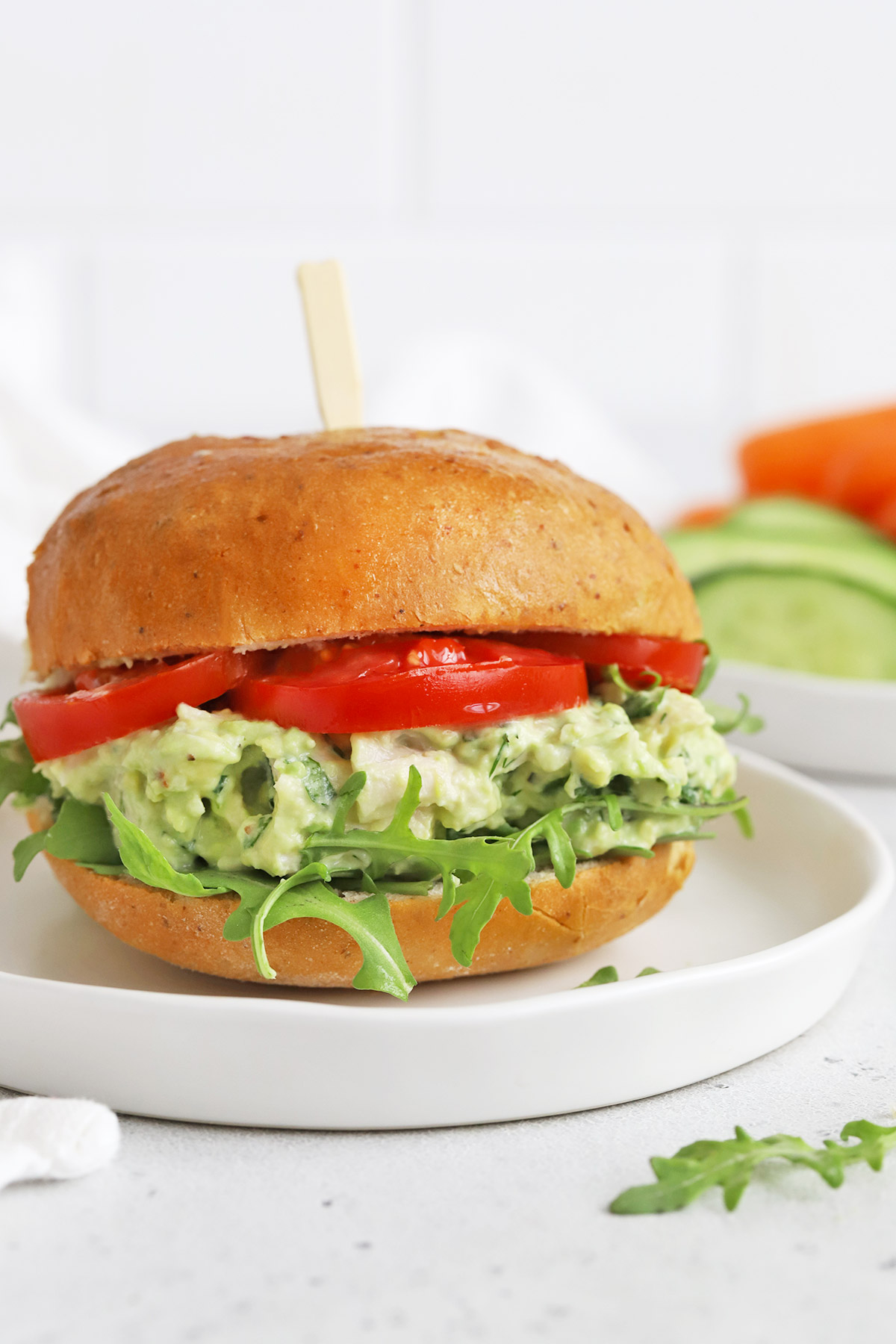 Close up front view of an avocado chicken salad sandwich with tomato and arugula on a white plate.