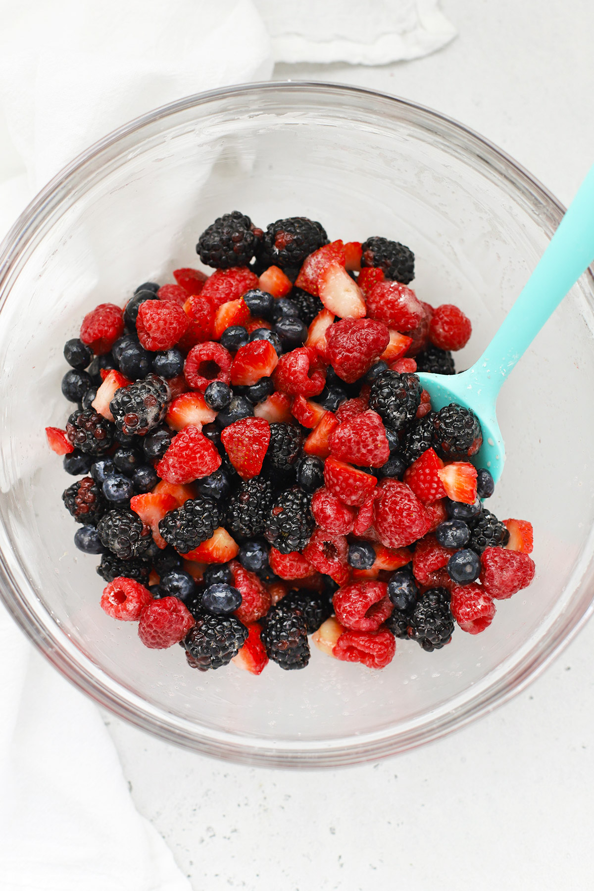 Overhead view of gluten-free mixed berry crisp filling in a glass mixing bowl