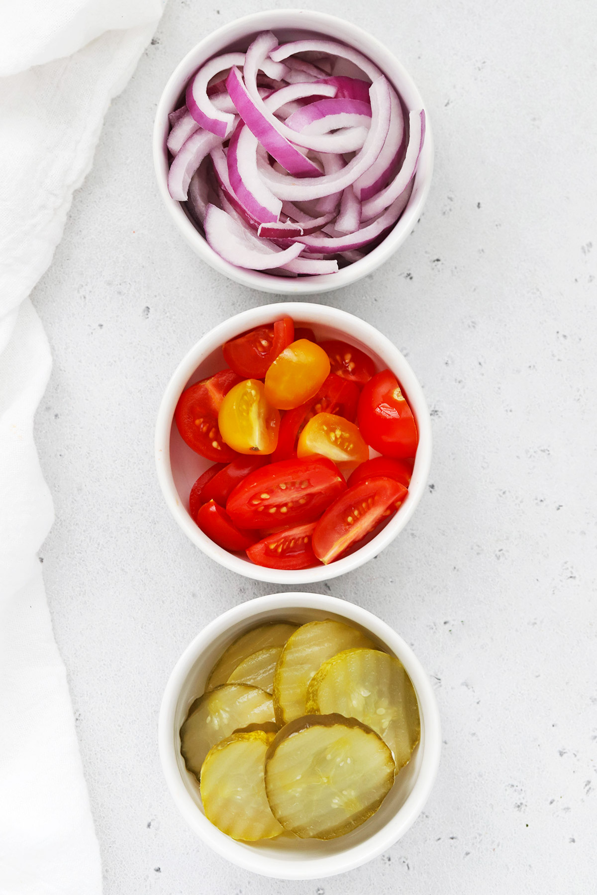 Overhead view of toppings for burger bowls--red onion, tomatoes, and pickles