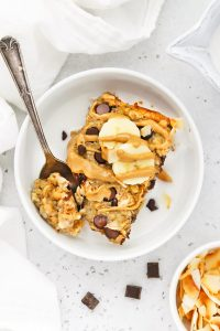 Overhead view of a bowl of Chunky Monkey Baked Oatmeal topped with bananas, drizzled peanut butter, and milk.