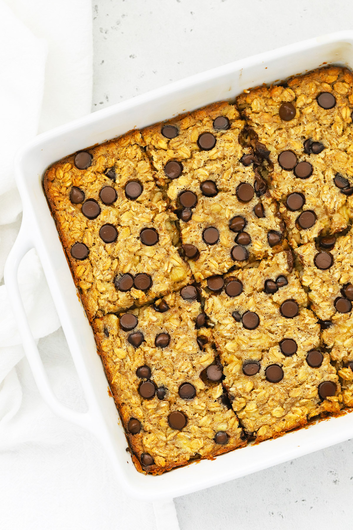 Overhead view of a pan of Chunky Monkey Baked Oatmeal sliced and ready to serve.