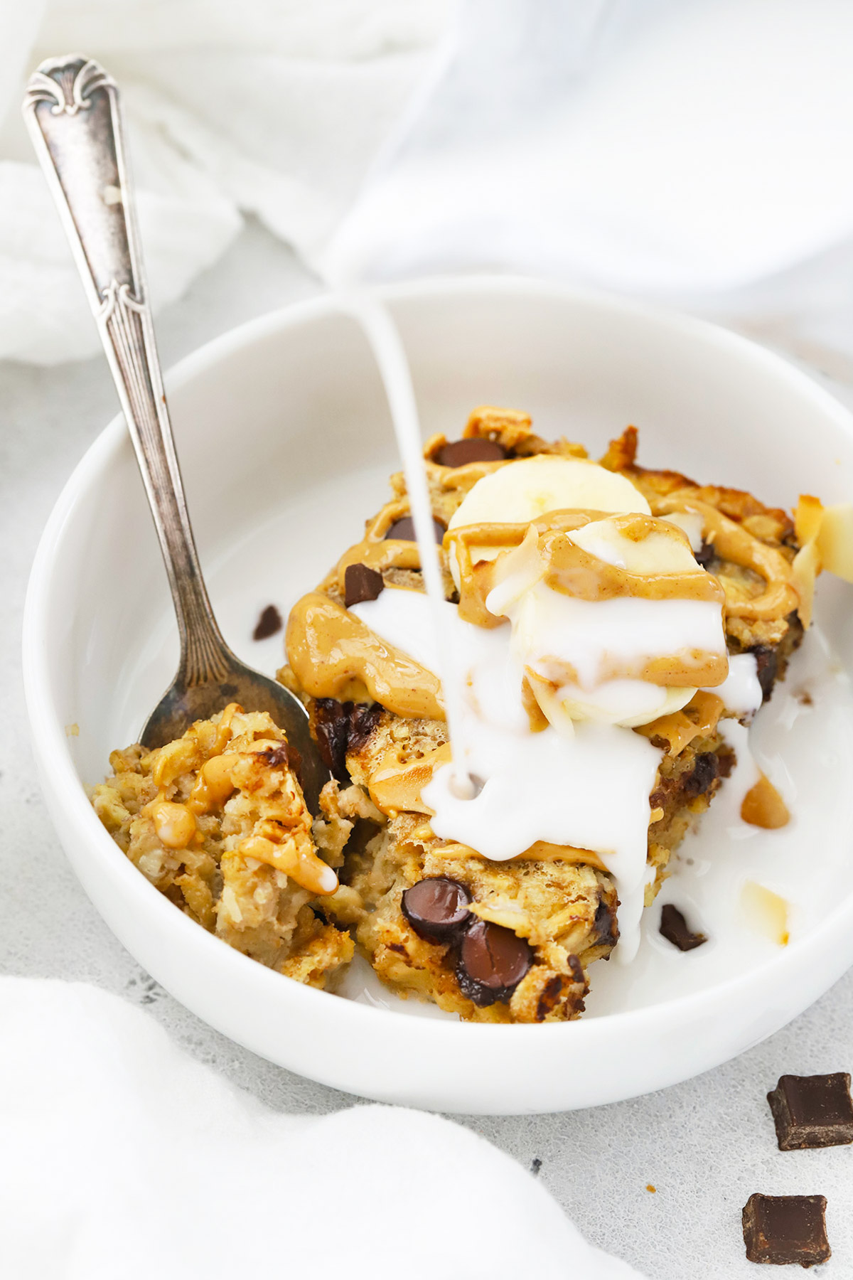 Front view of a bowl of Chunky Monkey Baked Oatmeal with milk being poured on top.