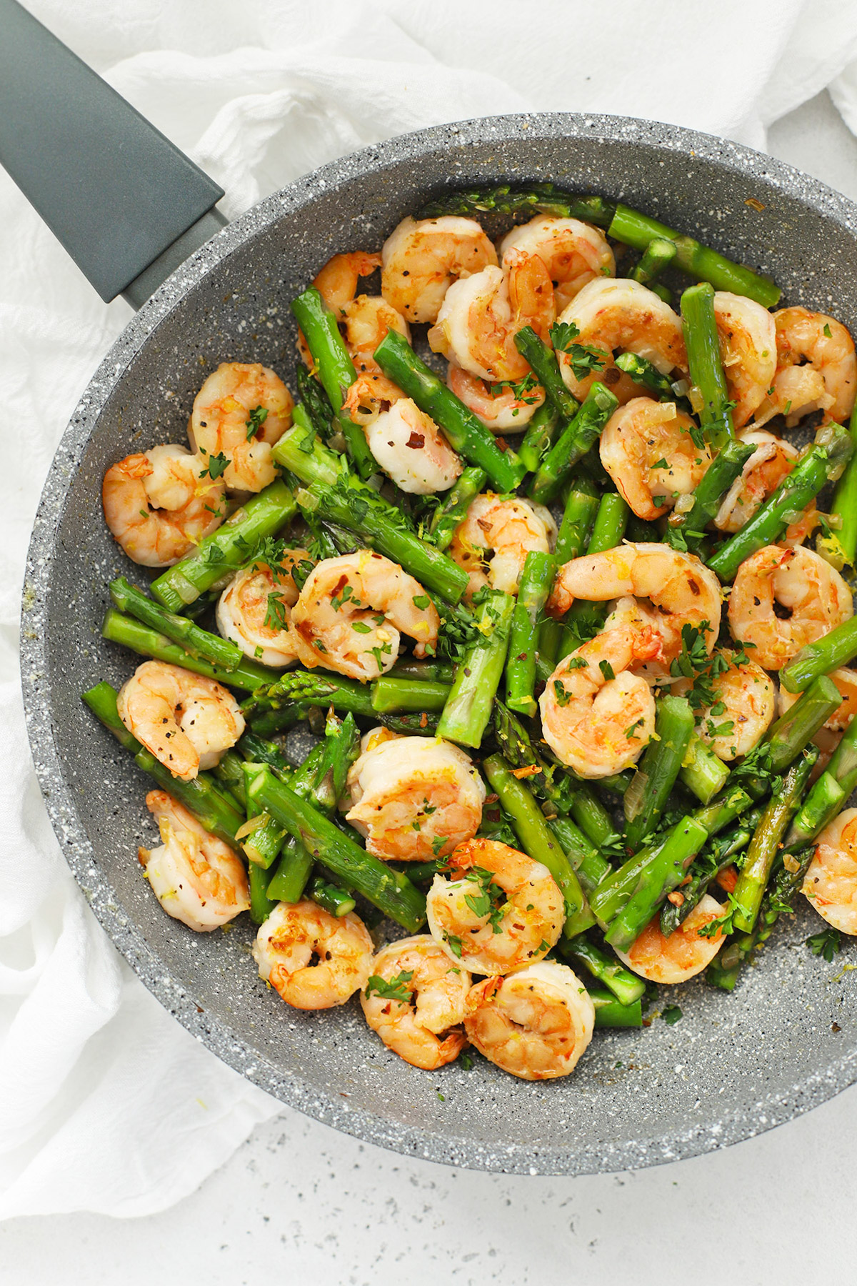 Overhead view of a skillet with lemon shrimp and asparagus