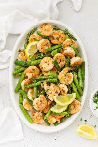 Overhead view of a platter of lemon shrimp and asparagus