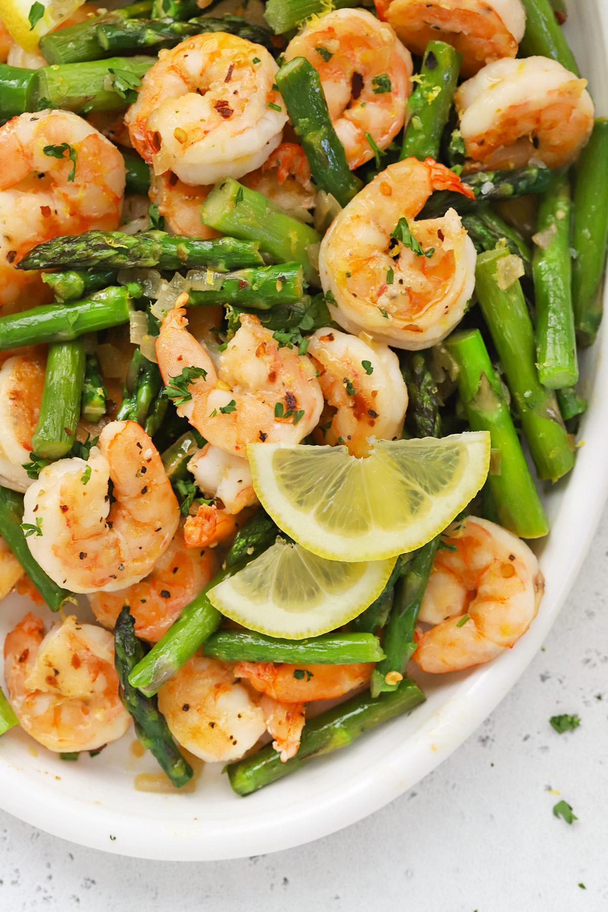 Close up overhead view of a platter of lemon shrimp and asparagus