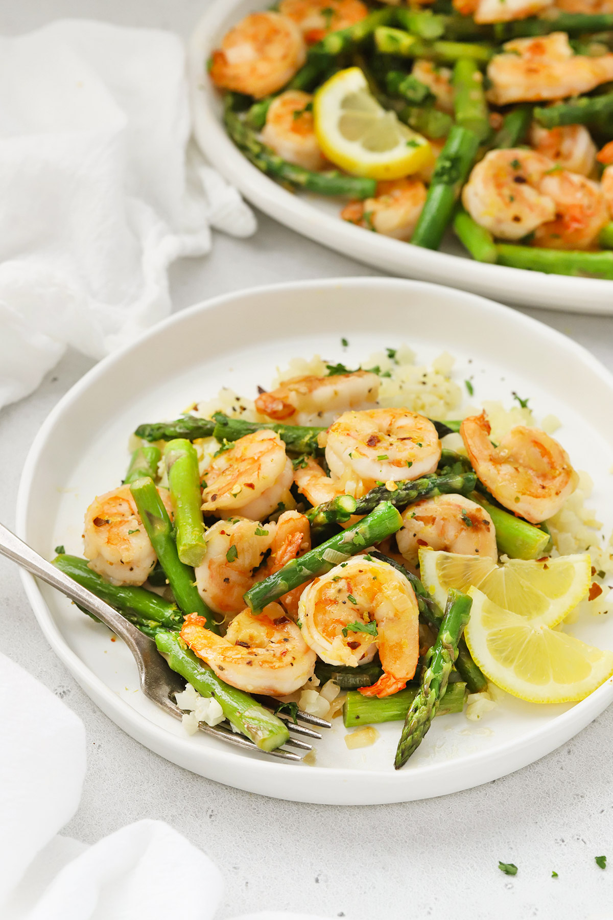 Front view of a plate of lemon shrimp and asparagus with cauliflower rice