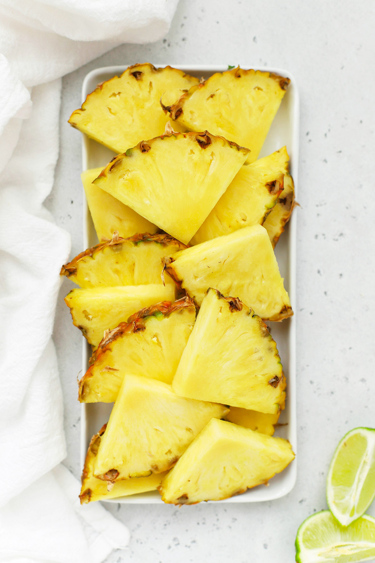 Overhead view of a rectangular platter of pineapple wedges on a white background