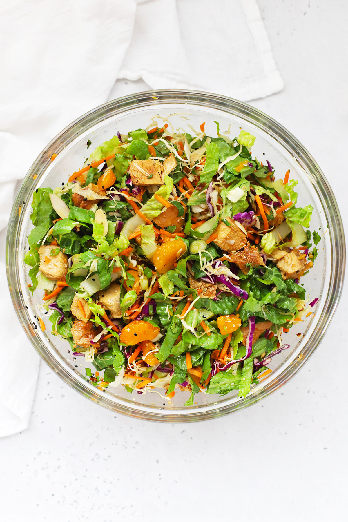 Overhead view of a mixing bowl of Sesame Chicken Salad on a white background