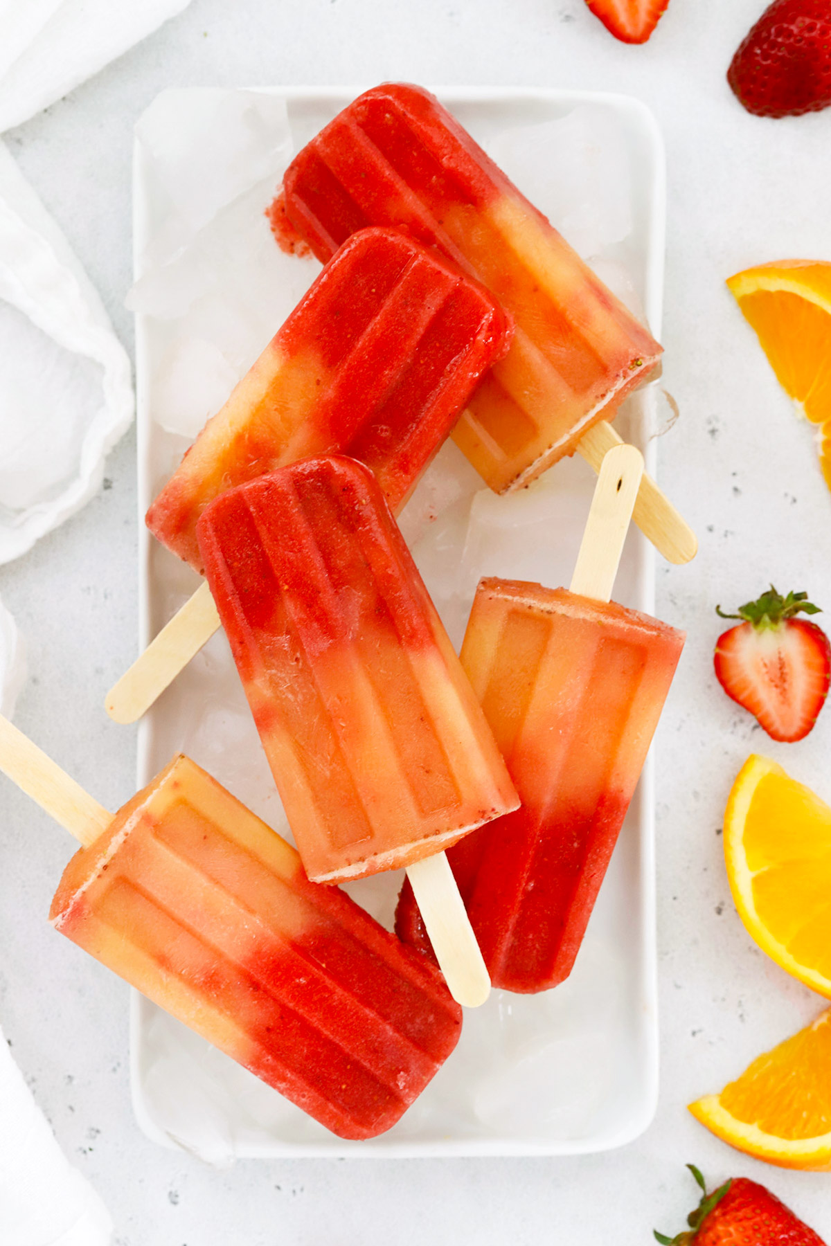 Overhead view of strawberry orange sunrise popsicles on a platter of ice