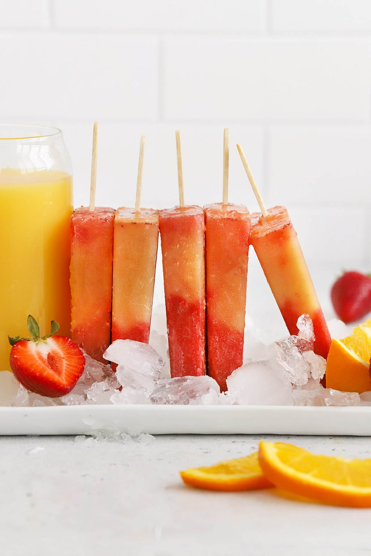 Front view of strawberry orange sunrise popsicles standing up in ice