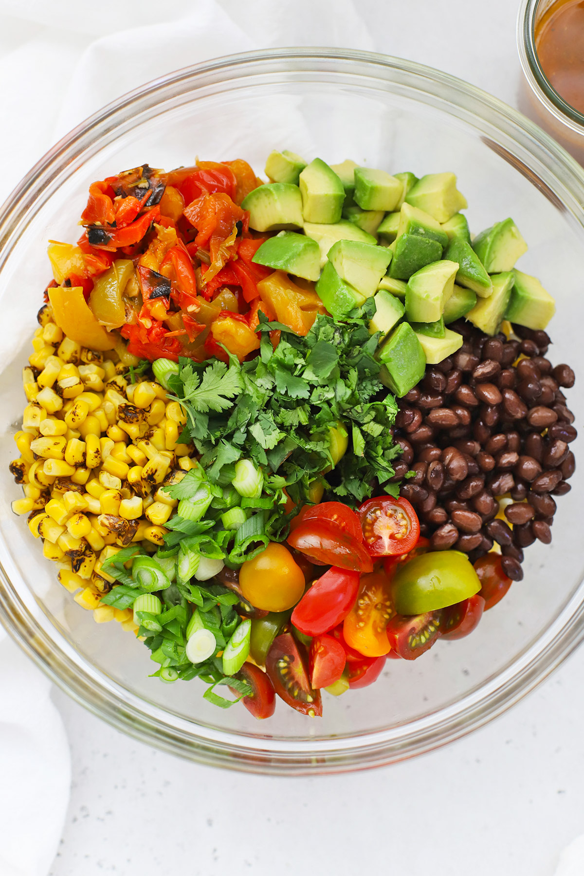Overhead view of a glass mixing bowl with ingredients for healthy taco pasta salad on a white background