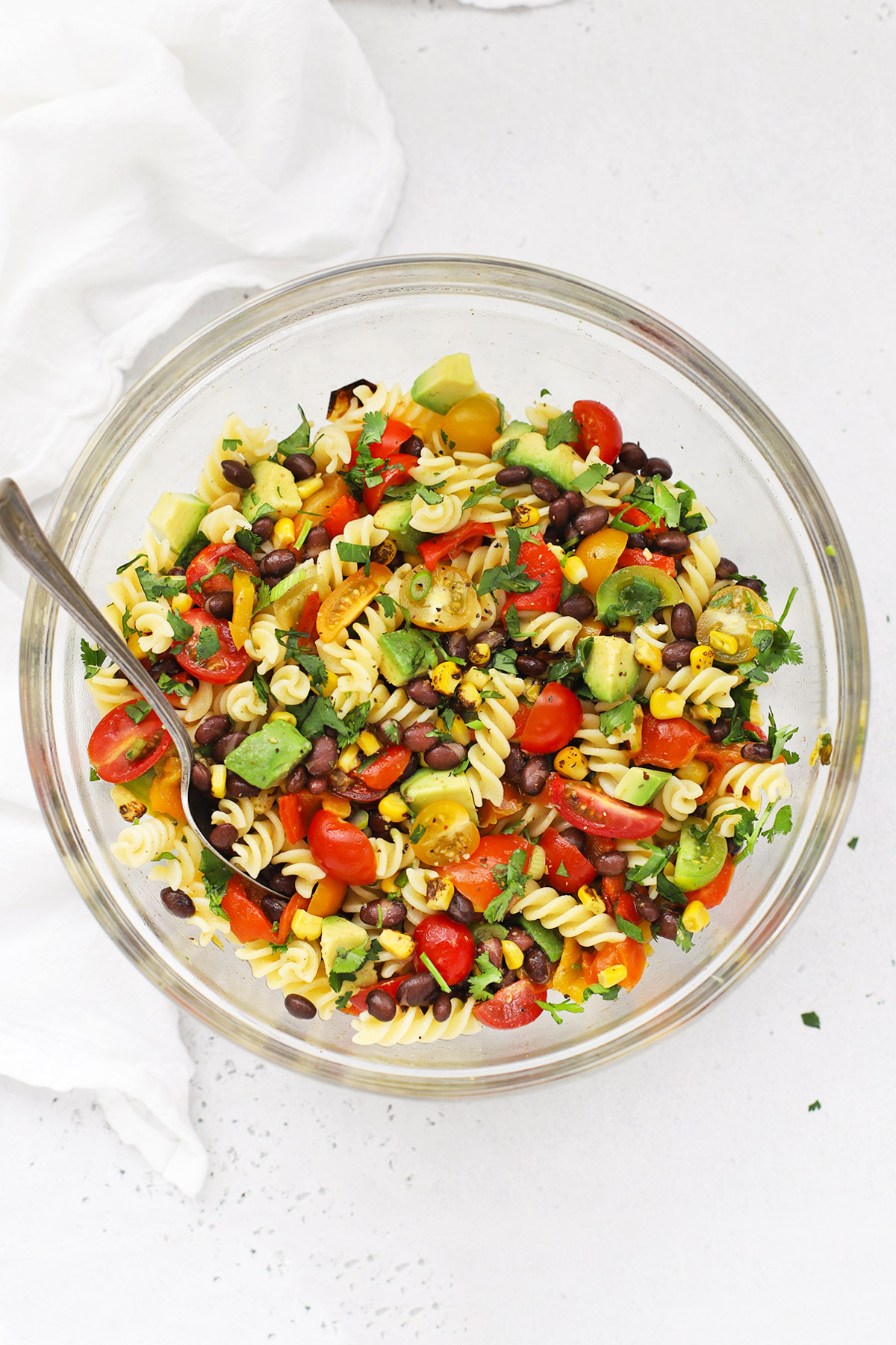 Overhead view of a glass mixing bowl of healthy taco pasta salad on a white background