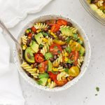 Overhead view of a speckled bowl of healthy taco pasta salad on a white background