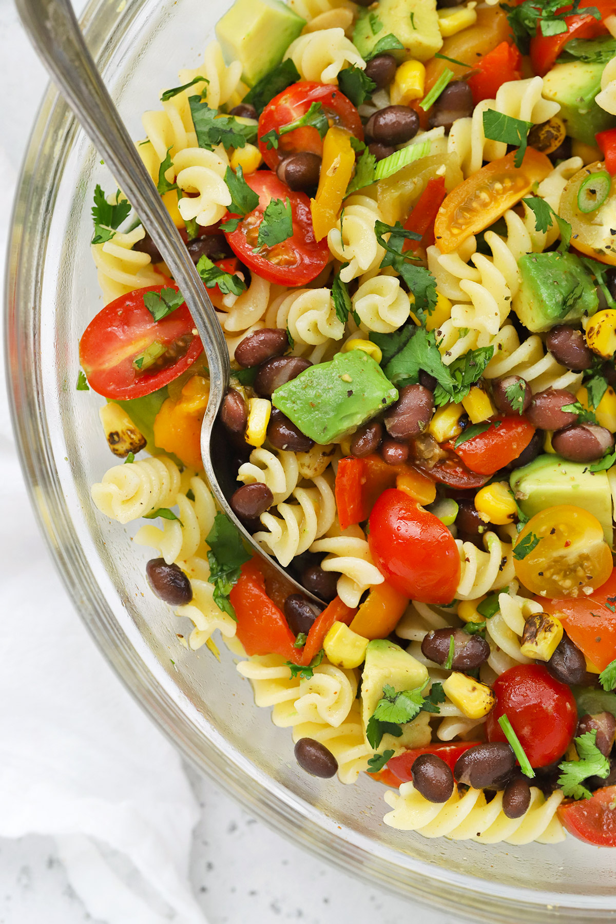 Close up Overhead view of a glass mixing bowl of healthy taco pasta salad on a white background