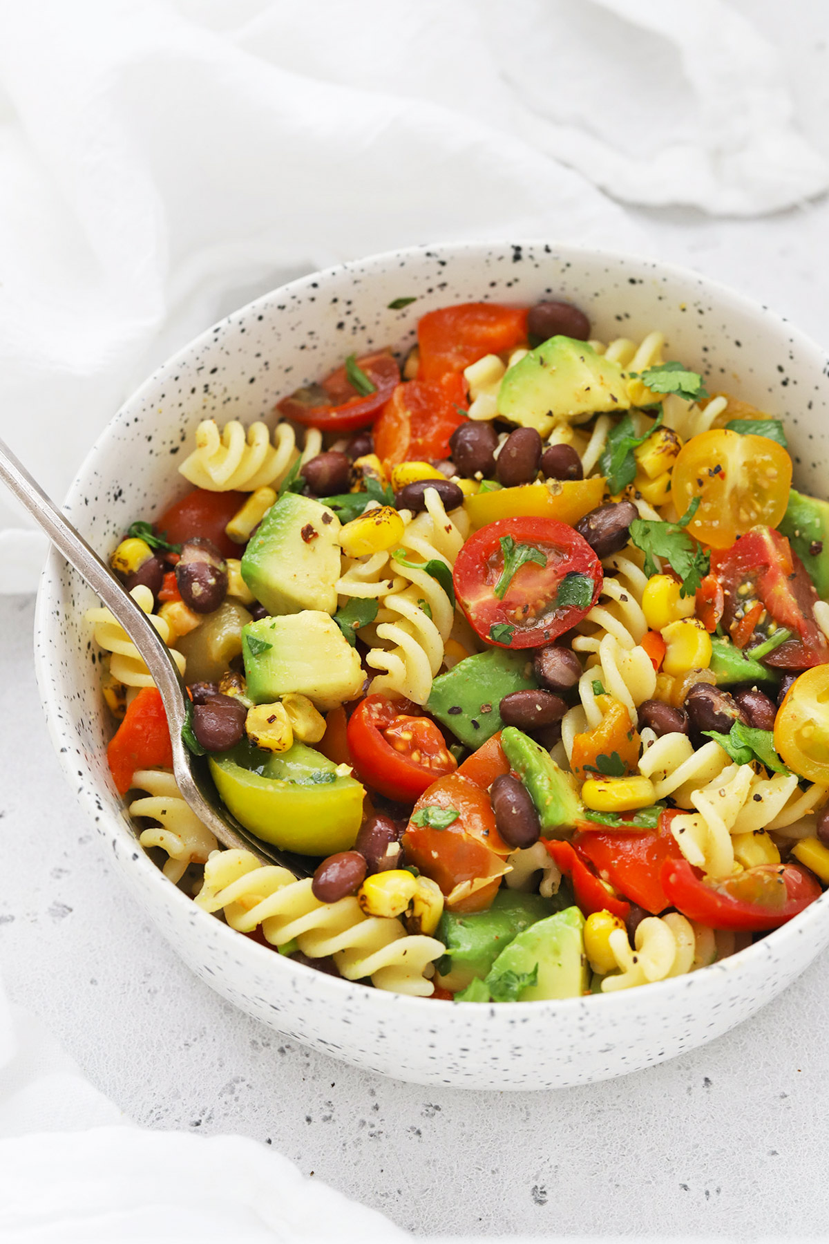 Front view of a speckled bowl of healthy taco pasta salad on a white background