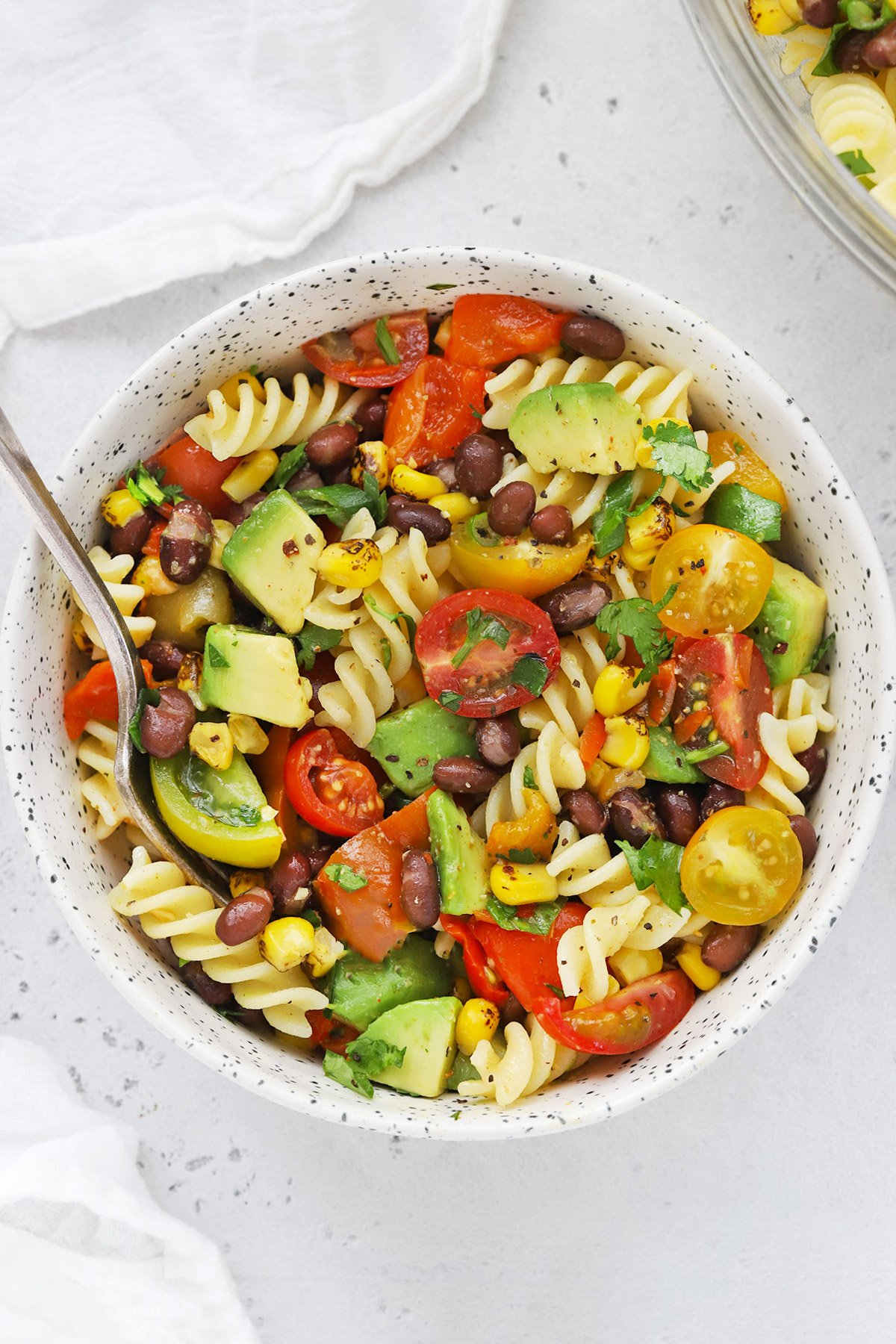 Close up Overhead view of a speckled bowl of healthy taco pasta salad on a white background