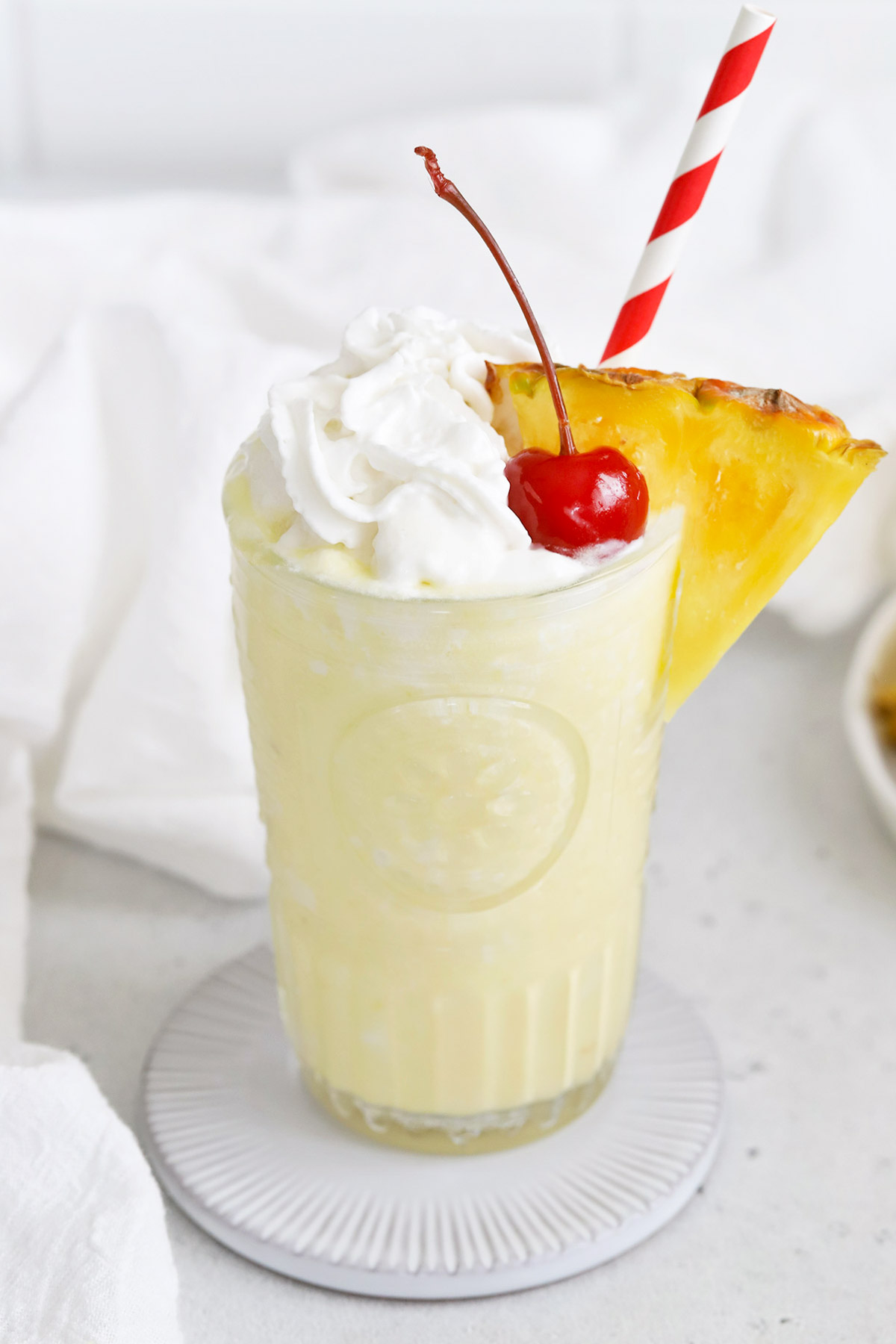 Close up front view of a virgin pina colada with whipped cream and a cherry on a white background