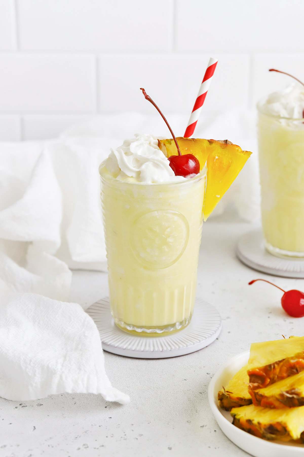 Front view of a virgin pina colada with whipped cream and a cherry on a white background