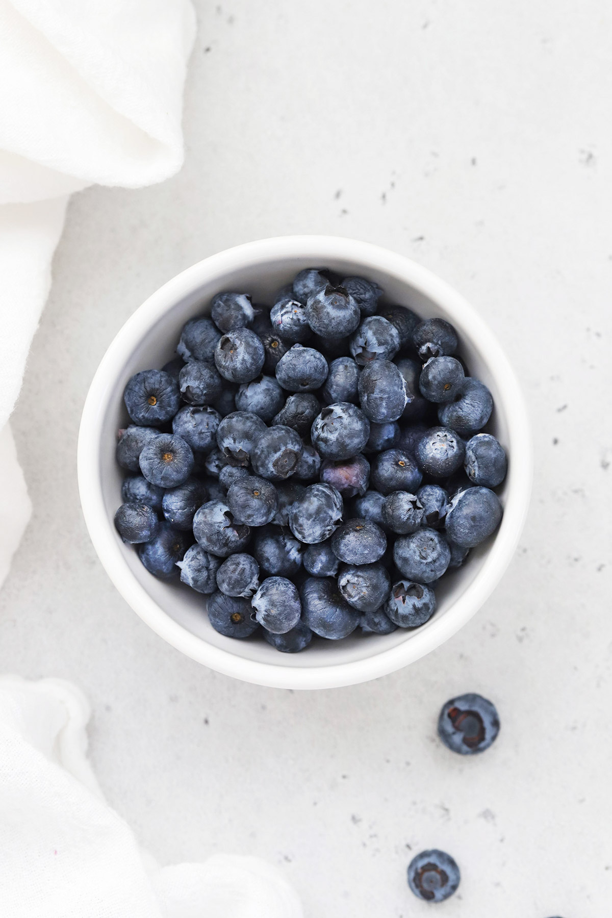 Overhead view of a small bowl of fresh, ripe blueberries on a white background