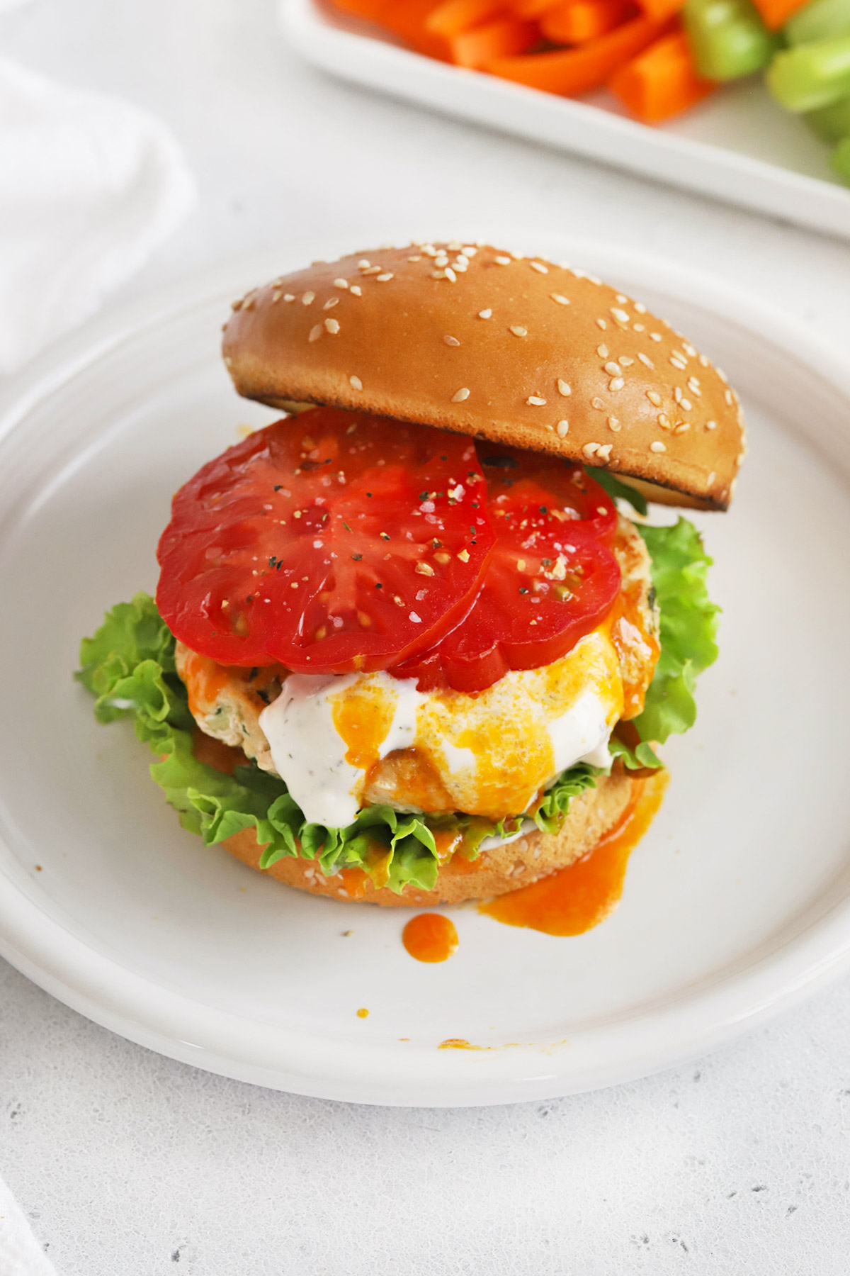 Overhead view of a buffalo chicken burger on a gluten-free bun with toppings just added to it.