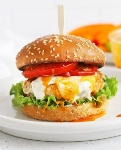 Close up front view of a buffalo chicken burger on a gluten-free bun with lettuce, tomato, buffalo sauce, and paleo ranch.