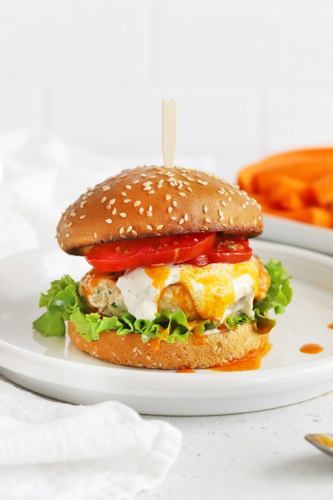 Front view of a buffalo chicken burger on a gluten-free bun with lettuce, tomato, buffalo sauce, and paleo ranch.