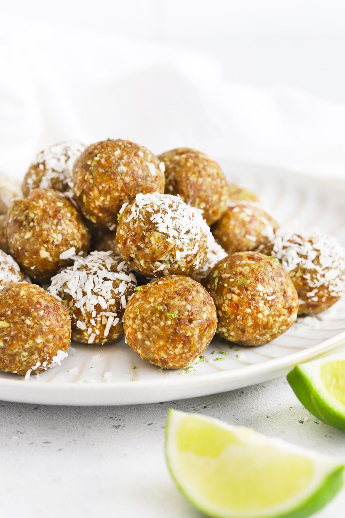 Front view of a plate of coconut lime energy bites. Some of them dipped in coconut.