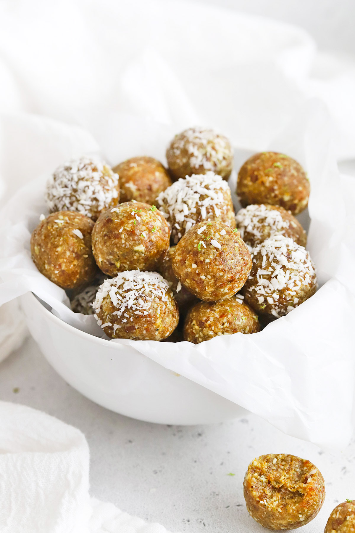 Front view of a bowl of coconut lime energy bites. Some of them dipped in coconut.
