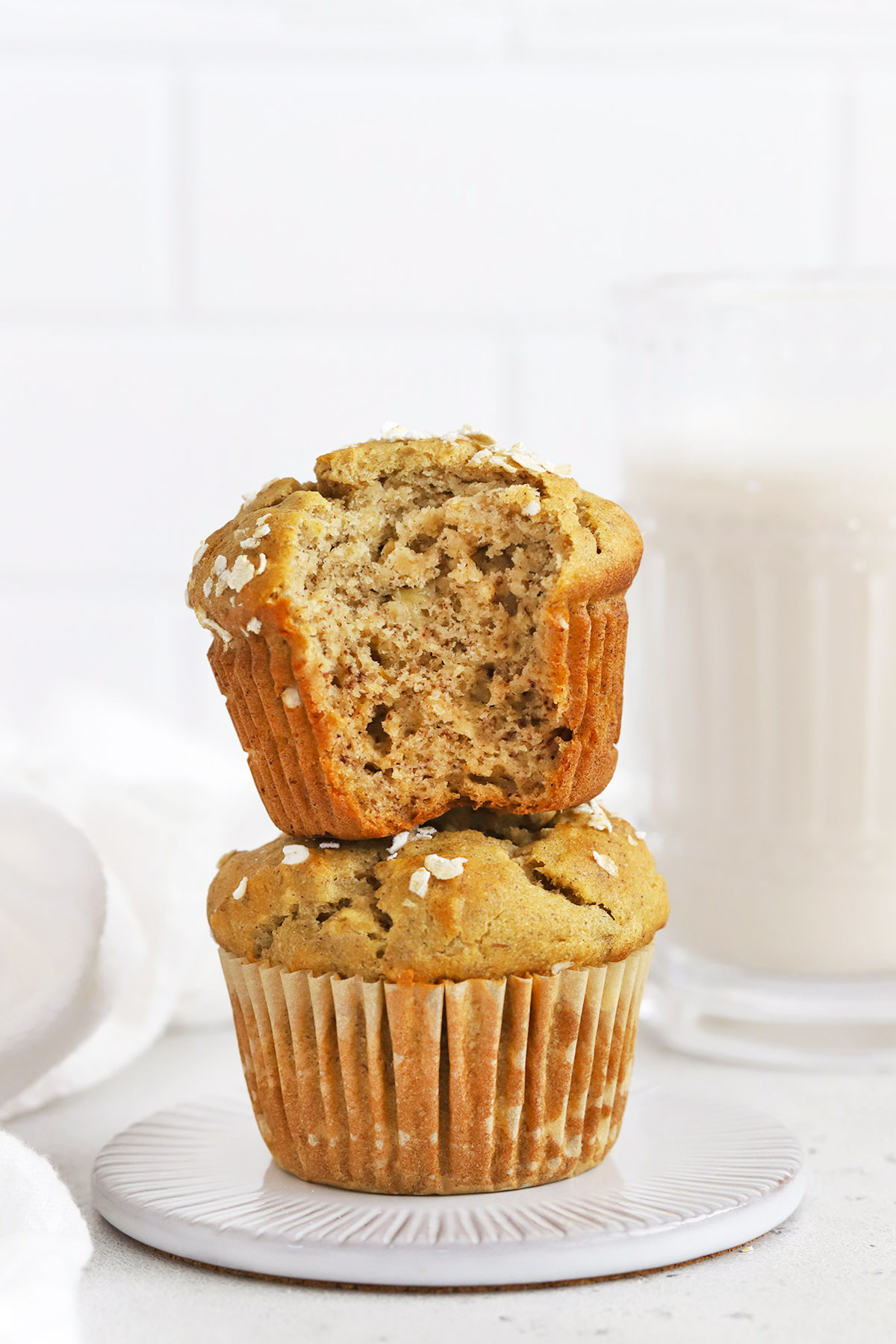 Front view of two gluten-free banana oatmeal muffins stacked on top of each other. The top muffin has a bite taken out of it.