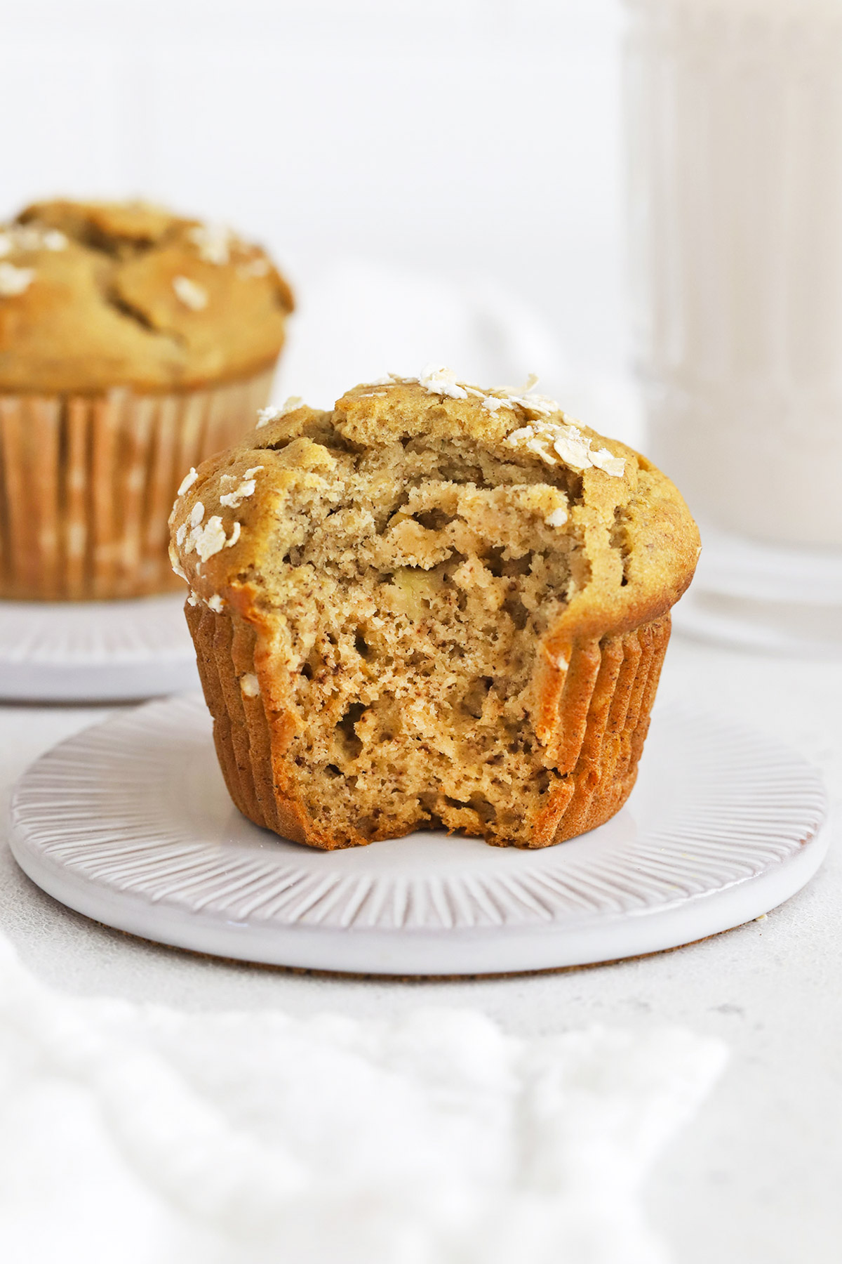 Front view of gluten-free banana oatmeal muffins. The one in the foreground has a bite taken out of it, showing a fluffy interior