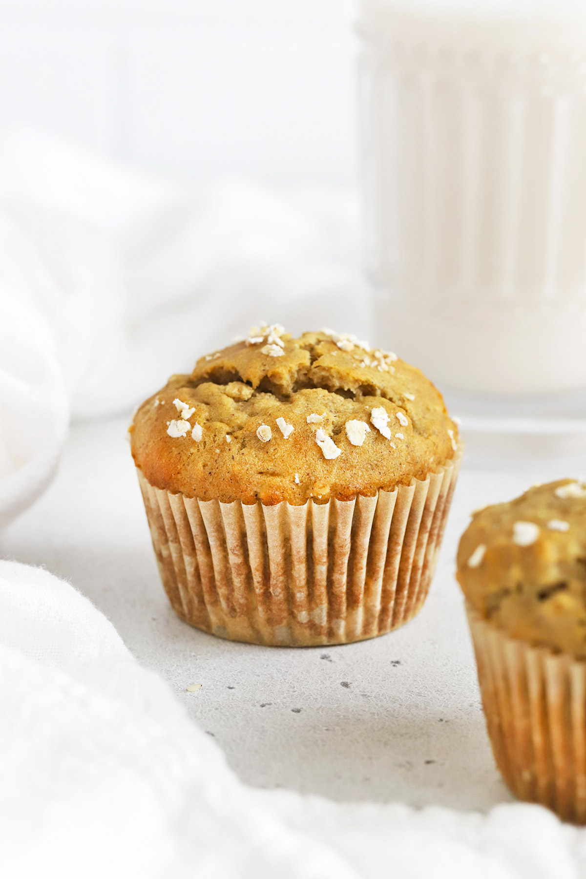Front view of a gluten-free banana oatmeal muffin on a white background. A glass of almond milk is visible in the background.
