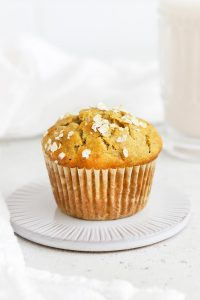 Front view of a banana oatmeal muffin on a coaster with a glass of almond milk in the background