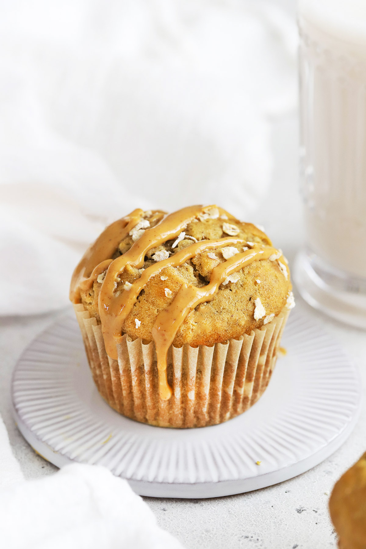 Front view of a gluten-free banana muffin drizzled with natural peanut butter