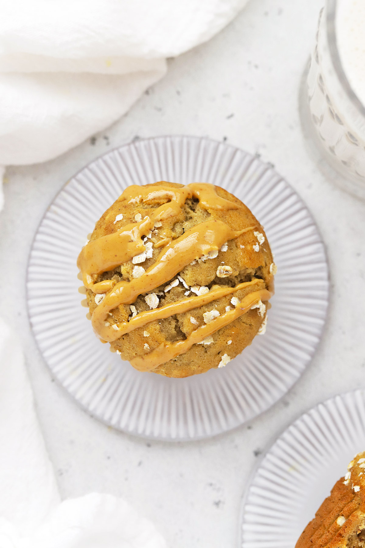 Overhead view of a gluten-free banana muffin drizzled with natural peanut butter