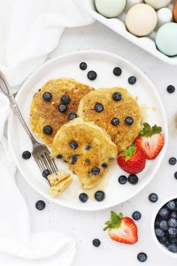 Overhead view of 3 fluffy gluten-free blueberry pancakes on a white plate drizzled with syrup