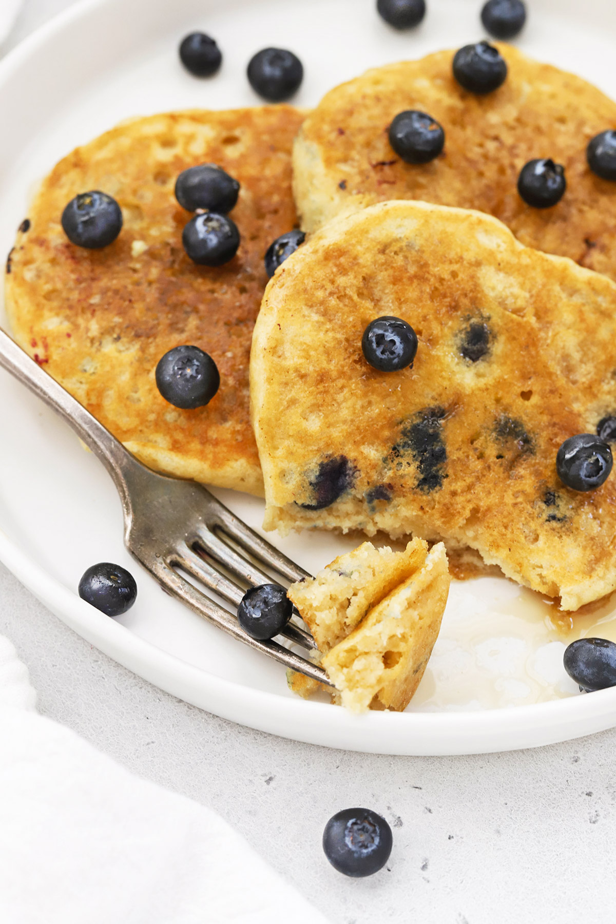 Close up view of 3 fluffy gluten-free blueberry pancakes on a white plate drizzled with syrup