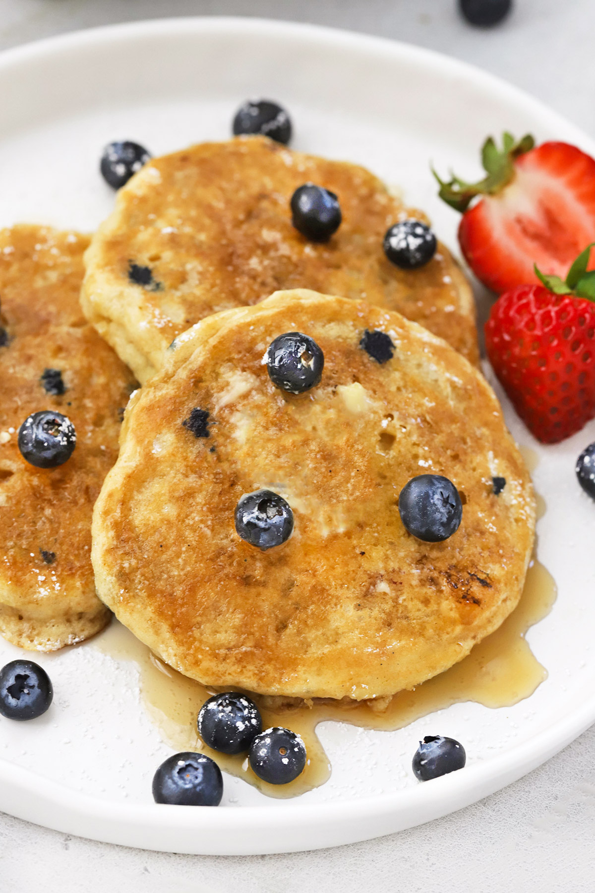 Front view of 3 fluffy gluten-free blueberry pancakes on a white plate drizzled with syrup