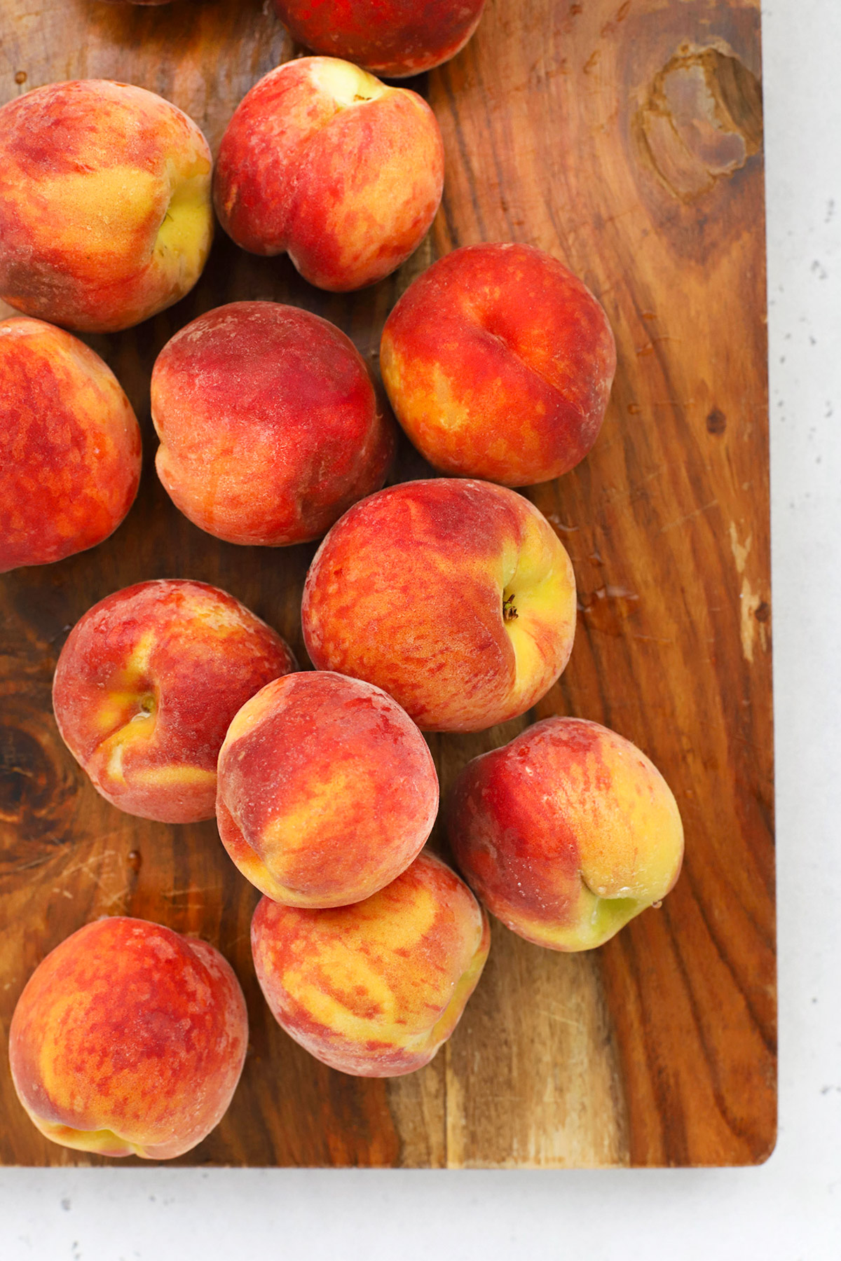Overhead view of fresh peaches on a wood cutting board