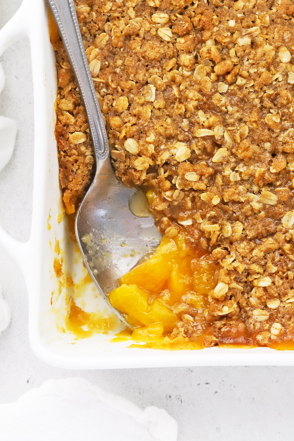 Overhead view of warm gluten-free peach crisp with a spoon in it, revealing colorful peach filling